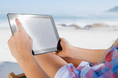 Woman sitting on beach in deck chair using tablet pc. On a sunny day Stock Photography