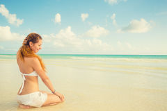 Woman sitting on a beach enjoying sunny day tropical weather Stock Images