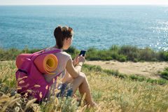 Woman sitting on the beach and enjoys phone Stock Image