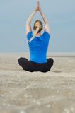 Woman sitting at beach with hands up in yoga position Stock Images