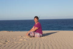 Woman sitting at the beach. Happy woman sitting in yoga posture at the beach Royalty Free Stock Photo