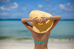 Woman sitting on beach holding hat Stock Photos