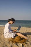 Woman sitting on beach with laptop Royalty Free Stock Photos