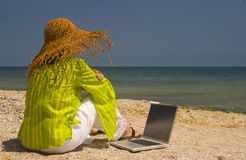 Woman sitting on beach with laptop. Woman in hat sitting on beach working on laptop stock photography