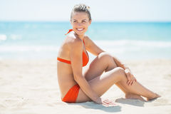 Woman sitting on beach and looking on copy space Royalty Free Stock Photos