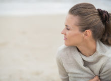 Woman sitting on beach and looking into distance Royalty Free Stock Images