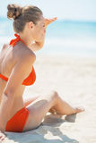 Woman sitting on beach and looking into distance Stock Photos