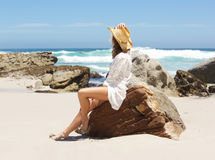 Woman sitting on beach looking at the sea Stock Images