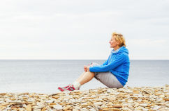 Woman sitting on the beach and looks into the distance Royalty Free Stock Photos