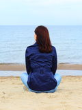 Woman sitting on the beach and looks at sea Stock Photo