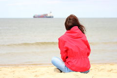 Woman sitting on the beach and looks at sea, summer time Stock Photography
