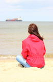 Woman sitting on the beach and looks at sea, summer time Stock Images