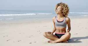 Woman Sitting On The Beach In Lotus Pose Stock Photos