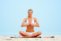 Woman sitting on the beach and meditating Stock Images