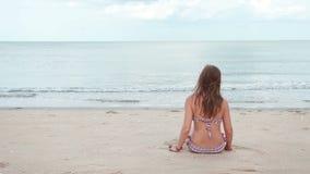 Woman sitting on the beach near the sea stock footage