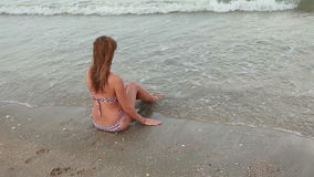 Woman sitting on the beach near the warm sea stock footage