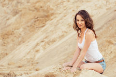 Woman sitting on beach Stock Images