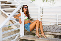 Woman sitting at the beach. Pretty young woman sitting on the steps at the beach Stock Image