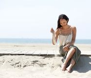 Woman sitting at the beach with sand in hand Stock Photography