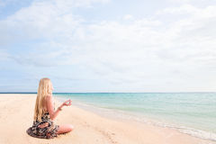 Woman sitting on beach sand and relaxing Stock Images