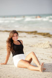 Woman sitting by the beach shore Stock Photo