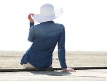 Woman sitting by beach with sun hat Stock Image