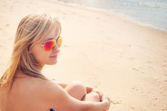Woman sitting on the beach in sunglasses Royalty Free Stock Photography