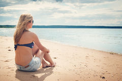Woman sitting on the beach in sunglasses Royalty Free Stock Image