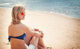 Woman sitting on the beach in sunglasses Royalty Free Stock Photo
