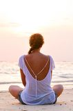 Woman is sitting on beach at sunrise. Young woman is sitting on beach at sunrise Stock Photo