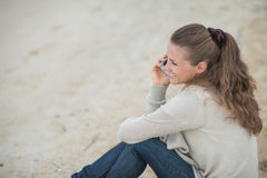 Woman sitting on beach and talking mobile phone Stock Photography