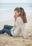 Woman sitting on beach and talking mobile phone Royalty Free Stock Photography