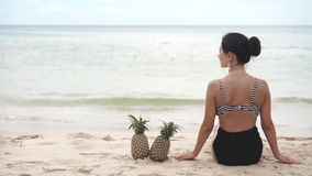 Woman sitting on the beach with two pineapples. Vacation on tropical beach in summer stock footage