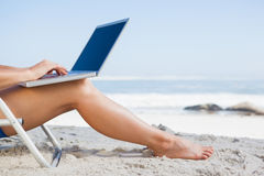 Woman sitting on beach using her laptop Royalty Free Stock Photography