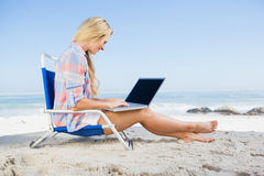 Woman sitting on beach using her laptop Stock Photo