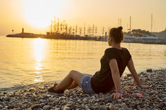 Woman sitting on the beach and watching the sunset Royalty Free Stock Photography