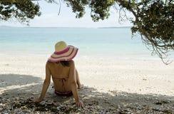 Woman sitting on beach wearing hat Stock Photo
