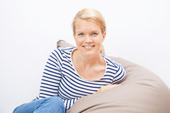 Woman sitting on a beanbag Stock Images