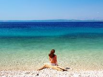 Woman sitting on the beautiful beach. Beautiful view of the beach.nPhoto taken on: July, 2016, Korcula, Croatia Royalty Free Stock Photo
