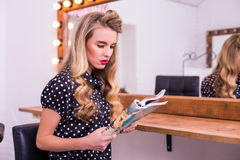 woman sitting in beauty salon and reading fashion magazine royalty free stock photography