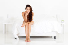 Woman sitting on bed Royalty Free Stock Image