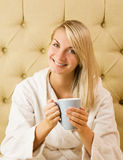 Woman sitting on a bed Stock Photography
