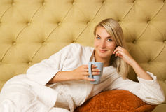 Woman sitting on a bed Stock Image