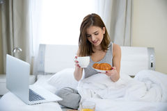 Woman sitting on the bed with breakfast Royalty Free Stock Photos