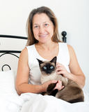 Woman sitting on   bed with  cat. Stock Photo