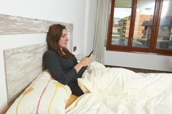 Woman sitting on bed chatting text message on smartphone. Woman sitting on bed chatting text message on smartphone wake up sleeping happy lifestyle lazy pillow royalty free stock image