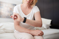 Woman sitting on bed checking time Royalty Free Stock Photos