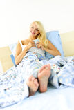 Woman sitting in bed with coffee cup Royalty Free Stock Photography