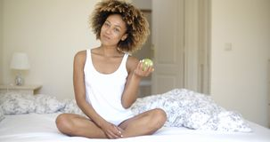 Woman Sitting On Bed And Eating Apple stock footage