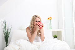 Woman sitting in bed enjoying coffee Stock Image